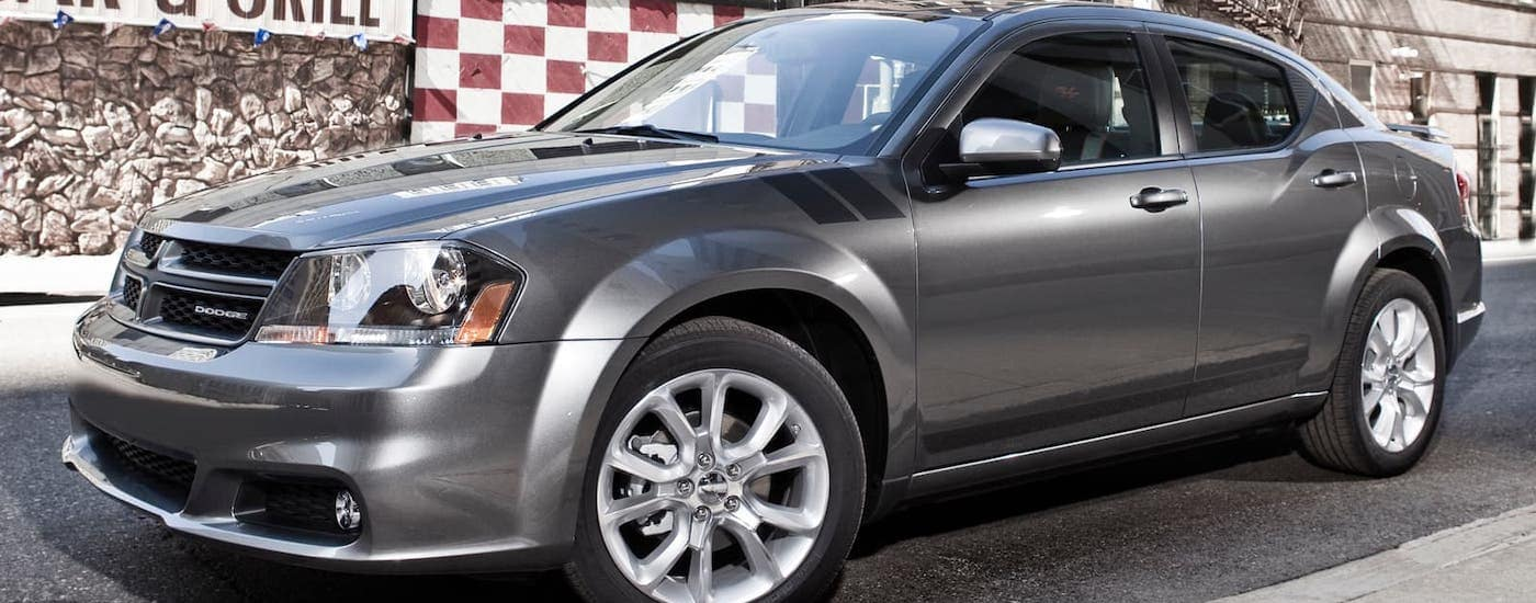 A silver 2014 Dodge Avenger from a used car dealership in Findlay, OH, is parked in front of a diner.