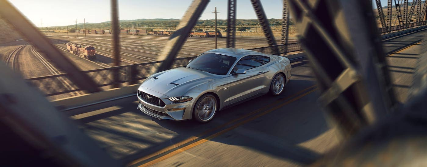 A silver 2018 Ford Mustang v8 GT from a used car dealership in Findlay, OH, is driving over a bridge.