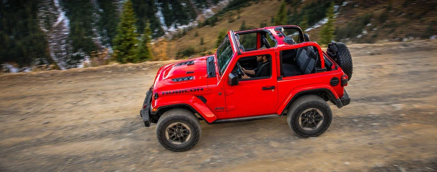 A red 2018 Jeep Wrangler Rubicon with no roof is driving on a dirt trail.