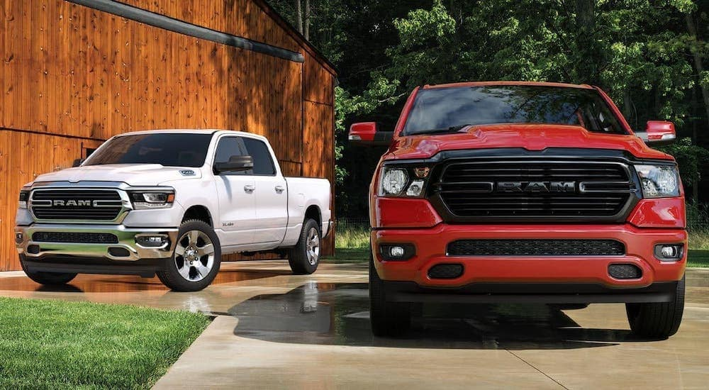 A red and a white 2020 Ram 1500s in front of a barn, find them at Ram Dealership Near Me in Findlay, OH.