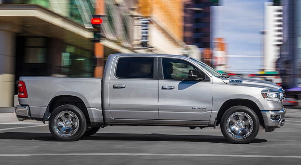 A silver 2020 Ram 1500 Big Horn is driving through a city intersection after leaving a Ram dealership near me.