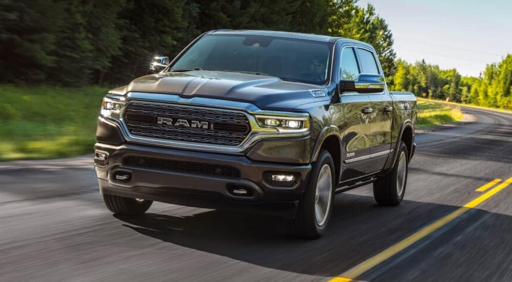 A grey 2020 Ram 1500 Limited is driving on a tree-lined street near Findlay, OH.