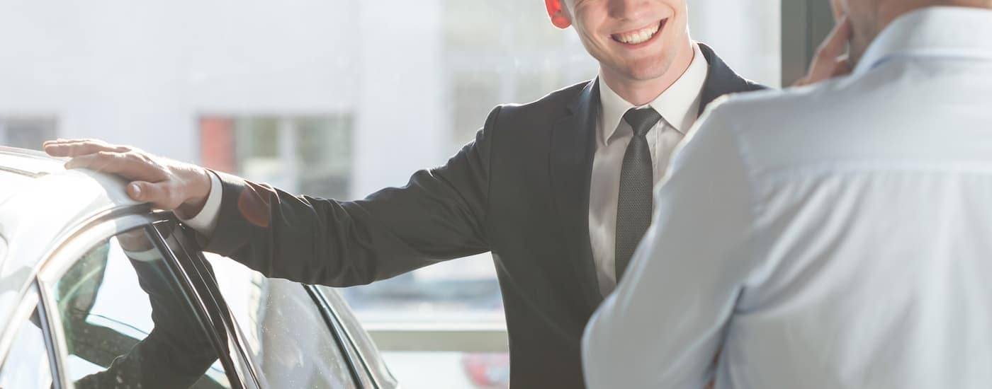 A salesman at one of the used car dealerships near me has his hand on the roof of a car while speaking with a customer.
