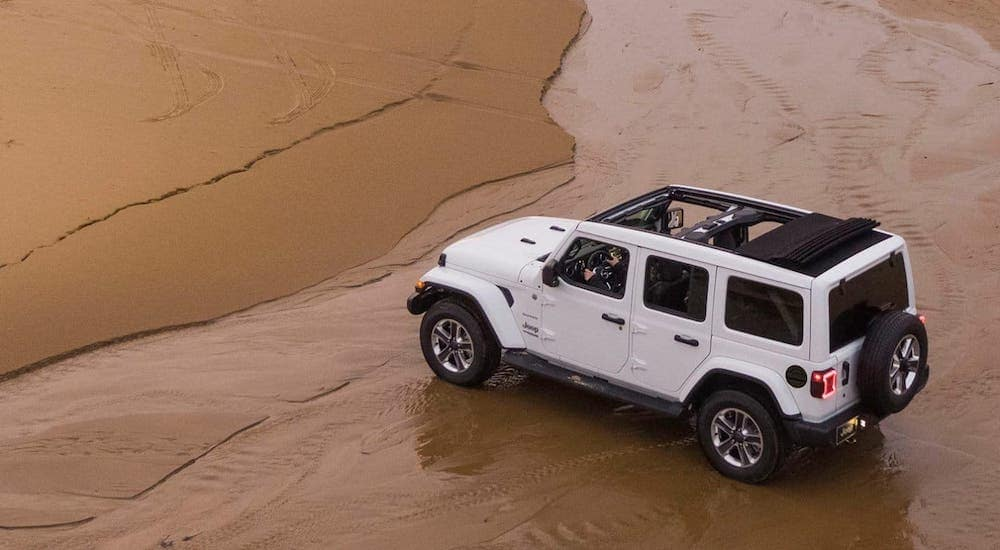 A white 2020 Jeep Wrangler Unlimited with the top open is shown from above at a beach.