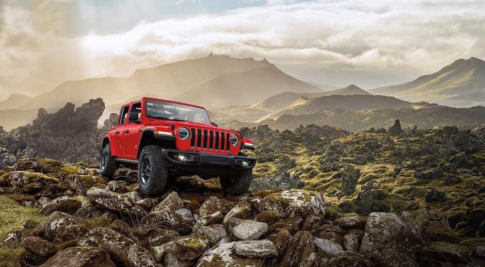 A red 2020 Jeep Wrangler Unlimited Rubicon with no roof from a Jeep dealer near me is climbing over rocks.