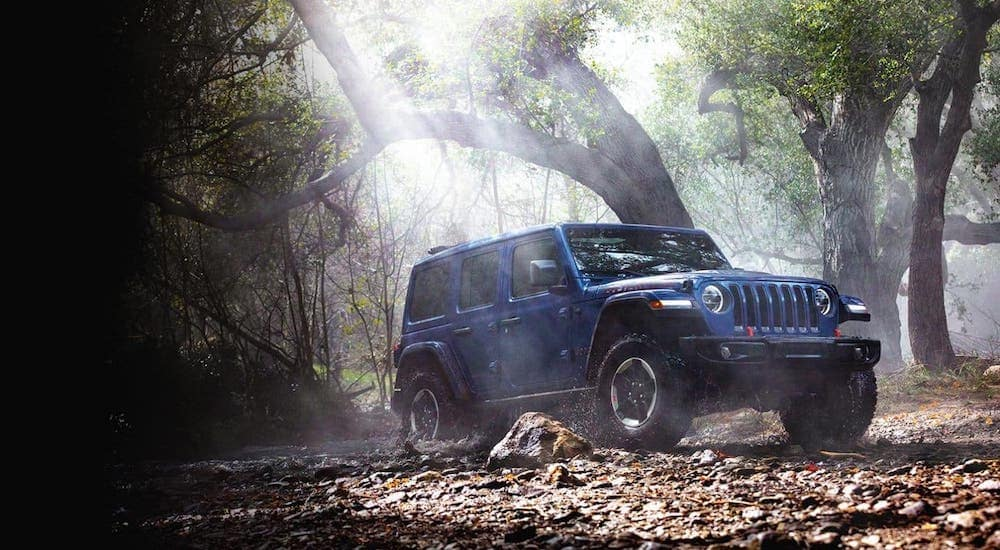 A blue 2020 Jeep Wrangler Unlimited Rubicon is crossing a river on a woodland trail near Findlay, OH.
