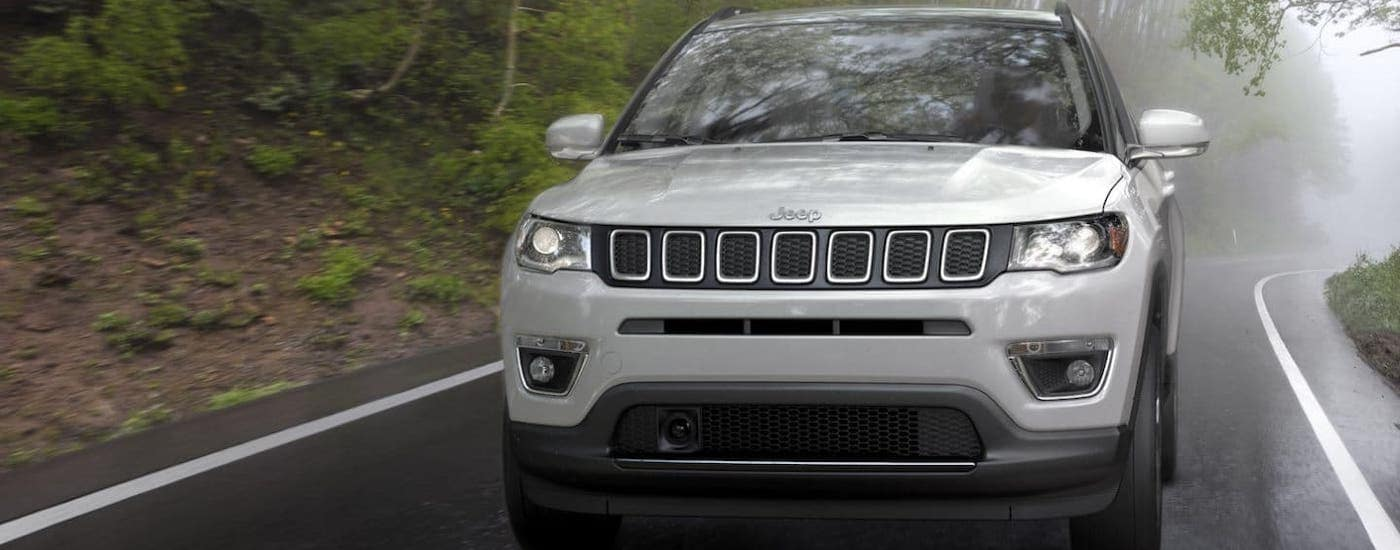 A silver 2020 Jeep Compass is shown from the front driving on a misty road.