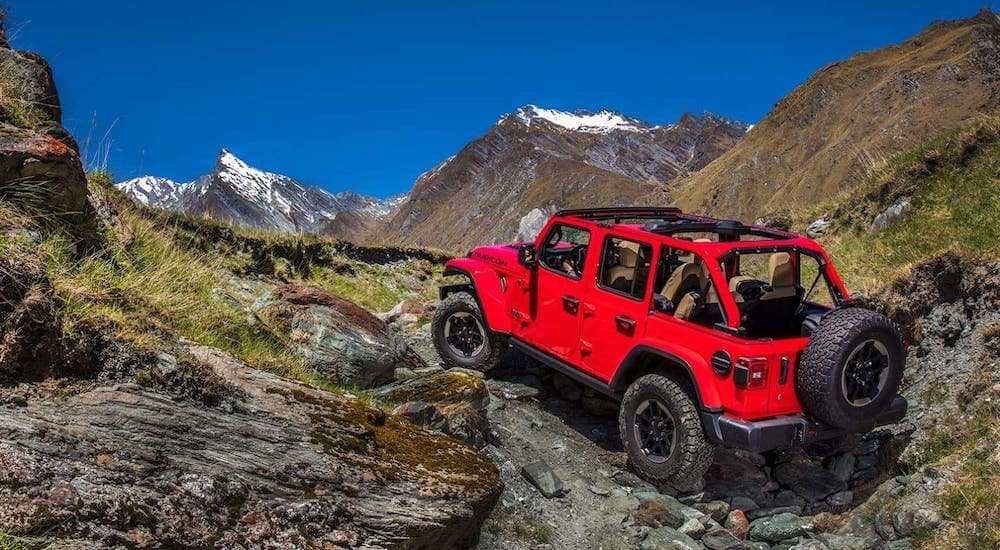 A red 2020 Jeep Wrangler Unlimited with no roof is climbing rocks on a mountain against a vibrant blue sky.