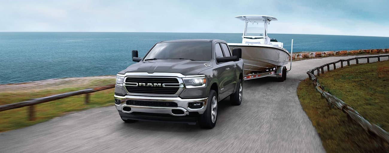 A grey 202 Ram 1500 is towing a boat around corner in front of the ocean after winning the 2020 Ram 1500 vs 2020 Chevy Silverado 1500 comparison.