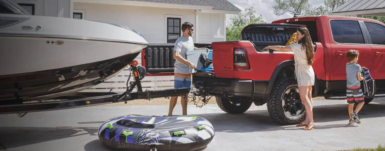 A family is loading up boating supplies in a red 2020 Ram 1500 with a Multifunction Tailgate in the driveway near Findlay, OH.