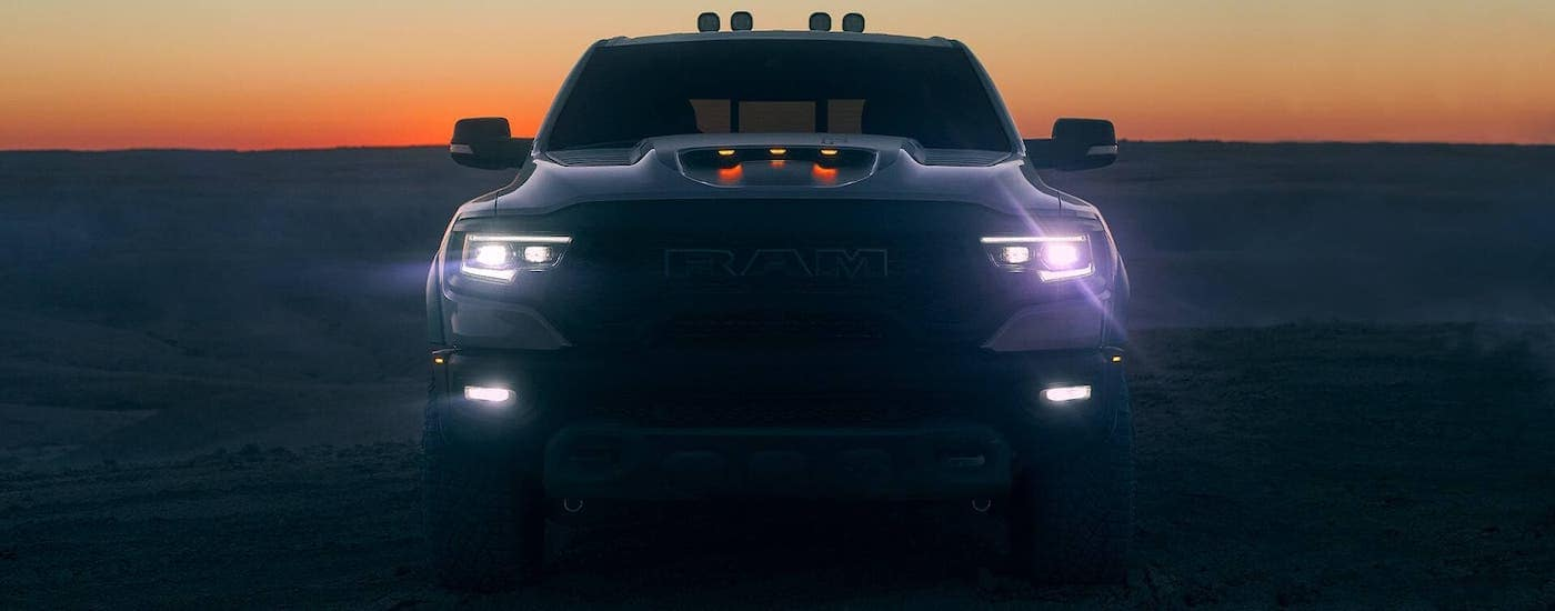 A white 2021 Ram TRX is shown from the front at dusk while parked in a sandy field near Findlay, OH.