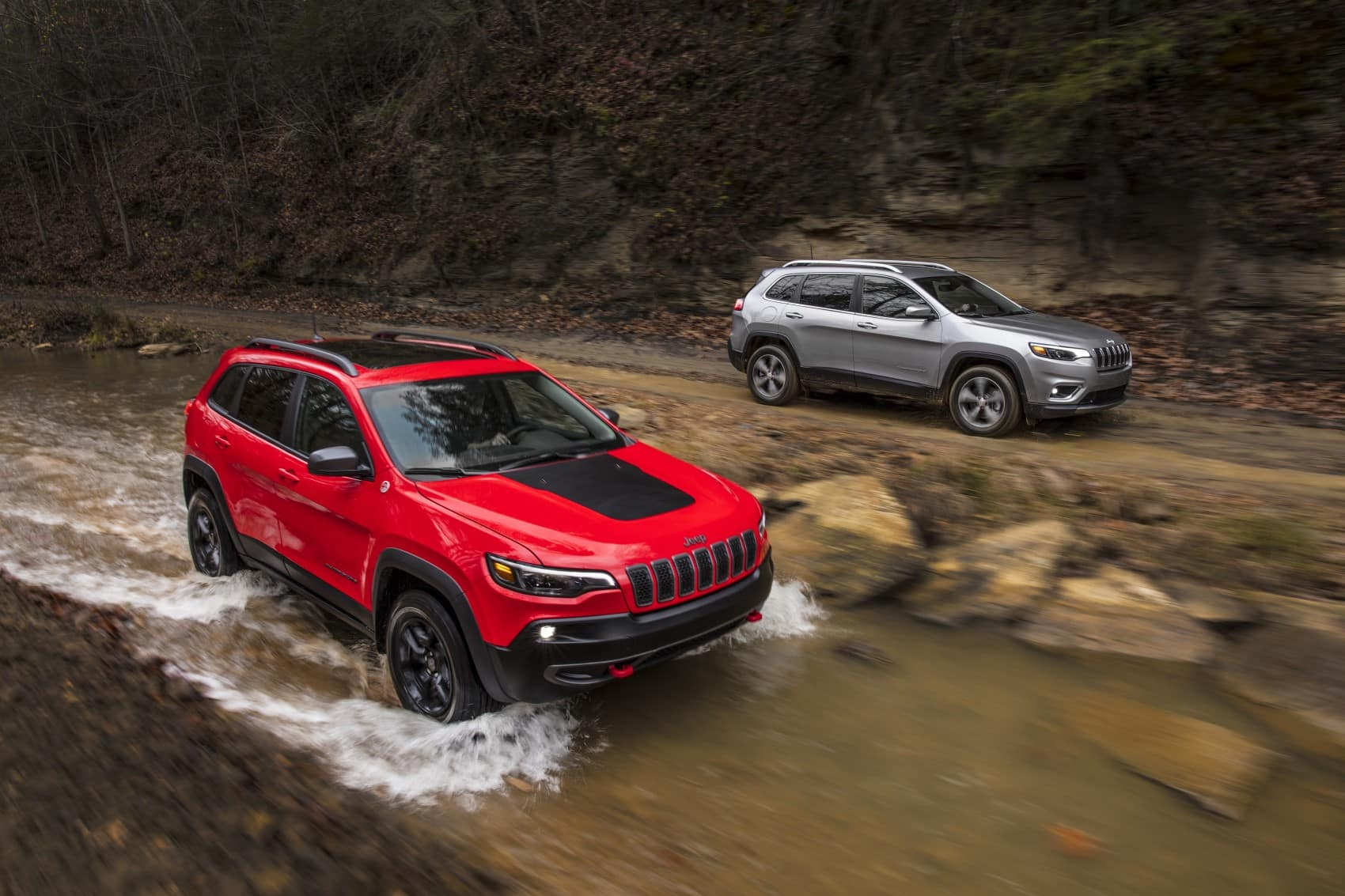 2021 Jeep Cherokee Trailhawk red and silver offroading in creek