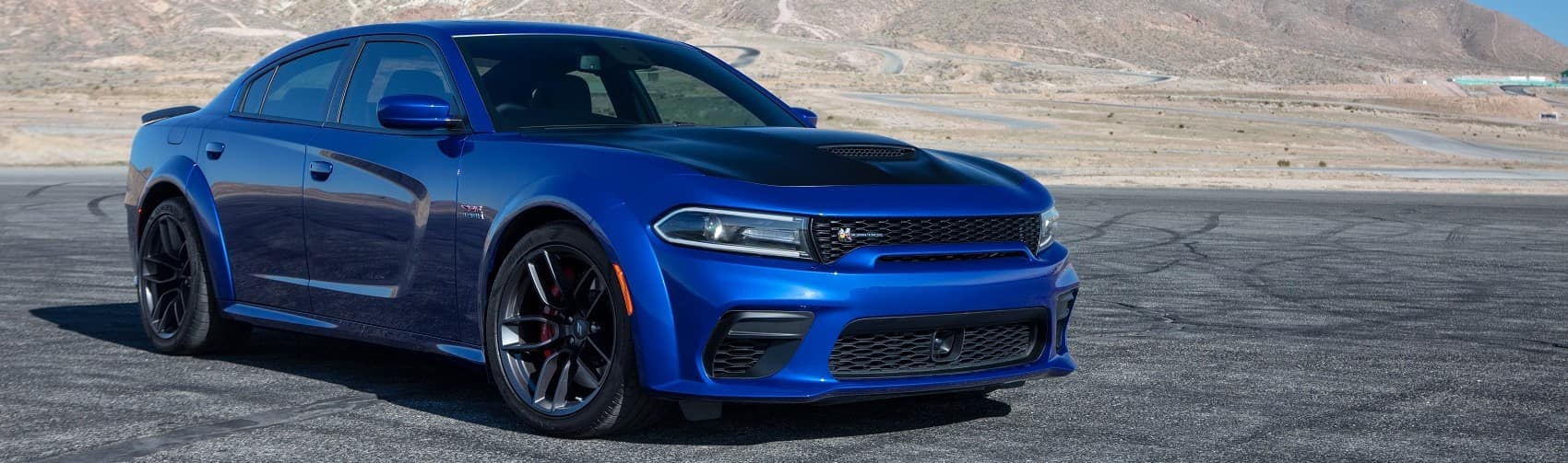 Dodge Charger widebody in front of western mountains banner