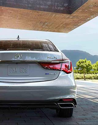 Silver Acura RLX under an overhang with a mountain in the distance