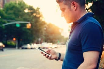 Man looking at cellphone on side of road