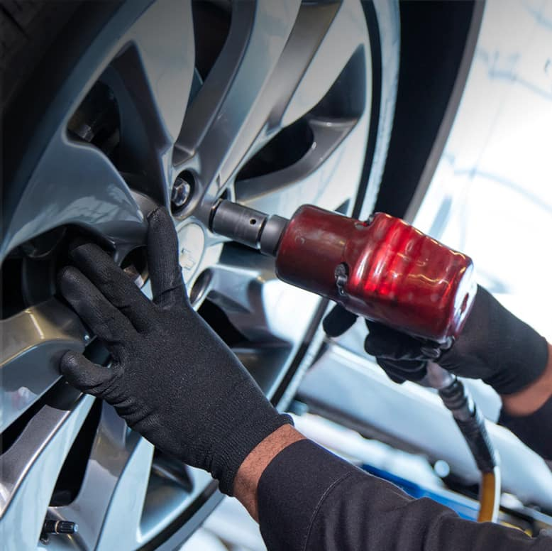 mechanic using an impact gun on a wheel lug nut