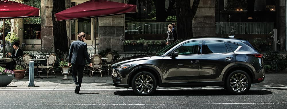 Man walking by Mazda CX-5 parked on side of road
