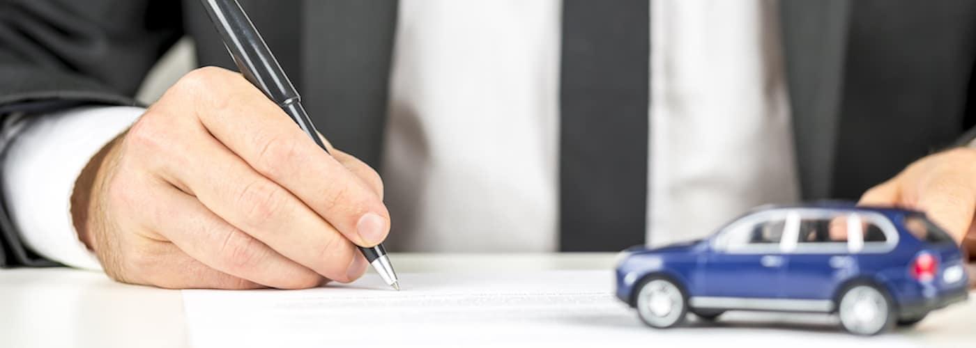 Man Signing Document at Car Dealership