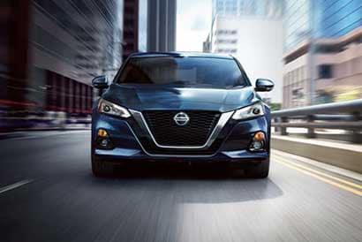 Black Nissan vehicle driving head-on through city environment