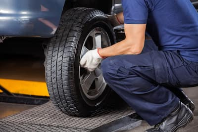 Mechanic Fixing Car Tire At Repair Shop