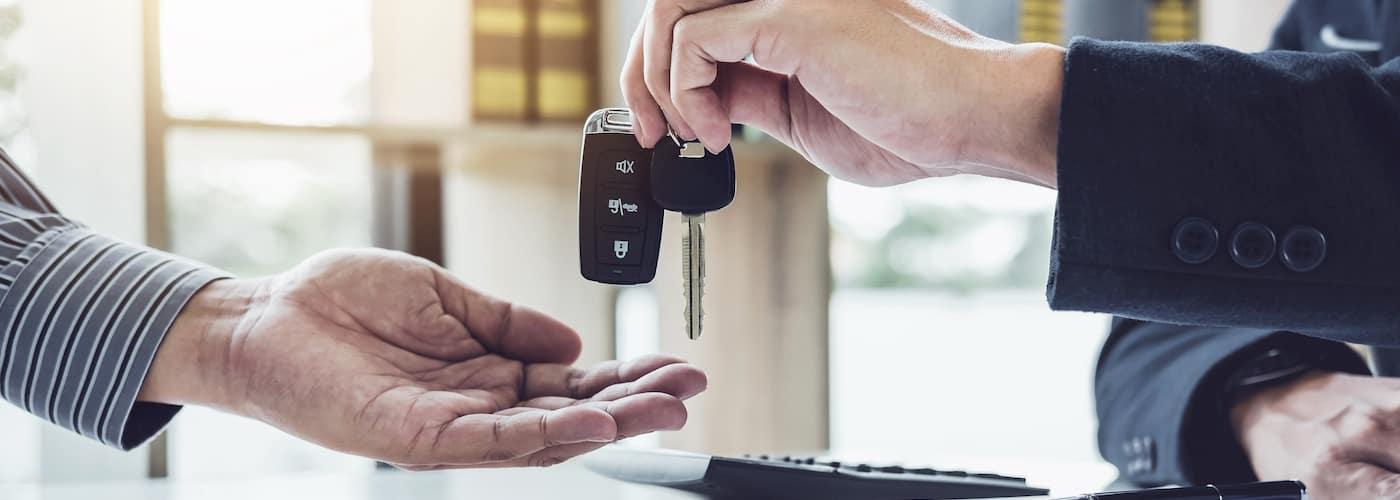 salesman handing keys over to client
